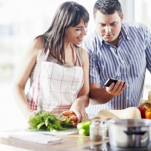 Un couple cuisinant et regardant un smartphone